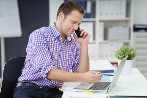 Man in purple and white checkered shirt answering phone calls and starring at laptop